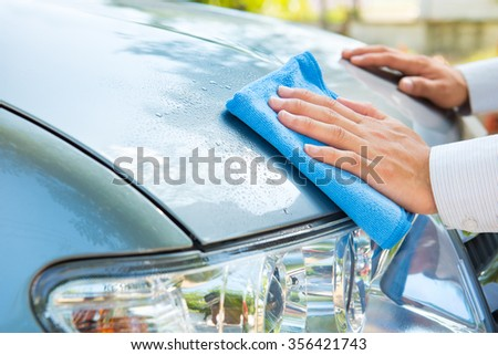 Hand cleaning car with microfiber cloth,wipe outside - stock photo