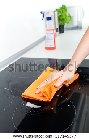 Hand cleaning induction stove - stock photo