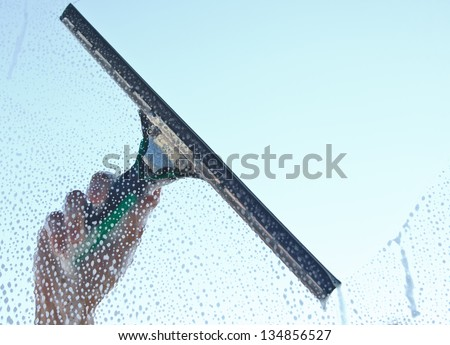 Hand cleaning window against blue sky in the background - stock photo