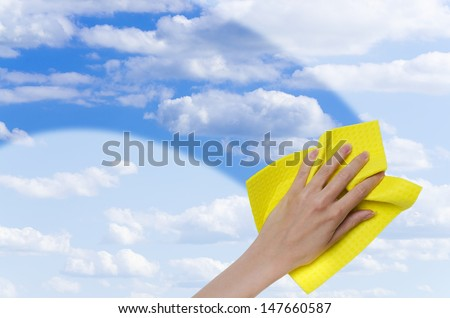 hand cleaning window making it easier to see blue sky through it - stock photo