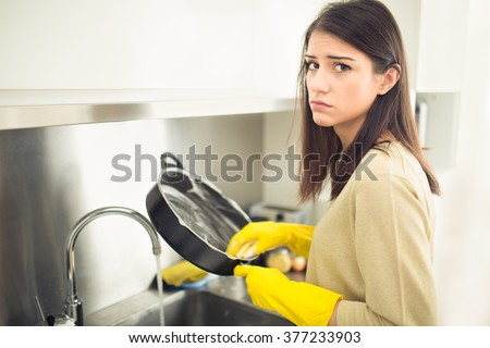 Hand cleaning.Young housewife woman washing dishes in kitchen.Young brunette woman washing dishes manually,by hand,wearing yellow cleaning rubber gloves.Tired of cleaning,making a sad face - stock photo