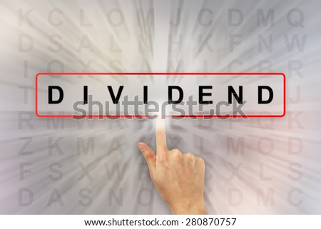 hand clicking dividend on word search puzzle - stock photo