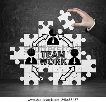hand collect puzzle with team work - stock photo