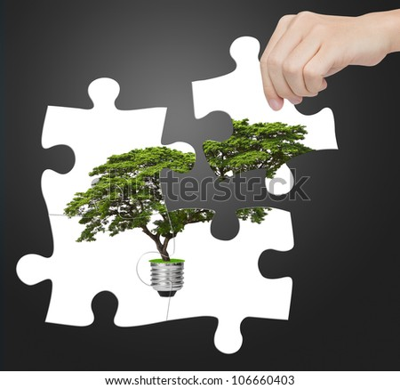 hand completing jigsaw puzzle of alternative green energy light bulb, sign of environment saving - stock photo
