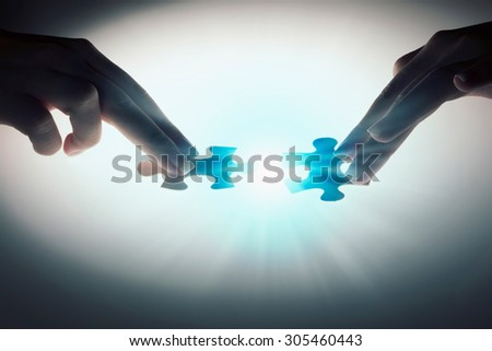 Hand connecting two jigsaw glowing puzzle pieces - stock photo