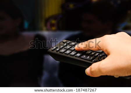 Hand control the remote background is a TV - stock photo