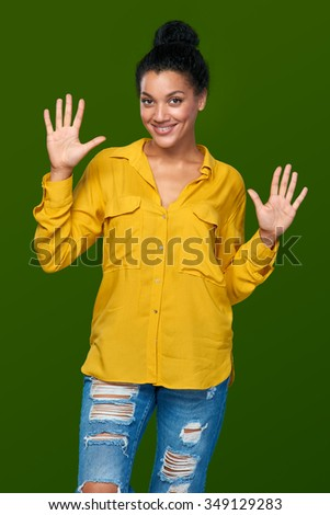 Hand counting - ten fingers. Happy mixed race african american - caucasian woman indicating the number ten with her fingers - stock photo