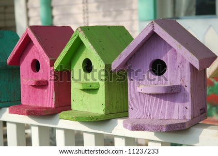 Hand crafted birdhouses are painted with pastel colors. - stock photo