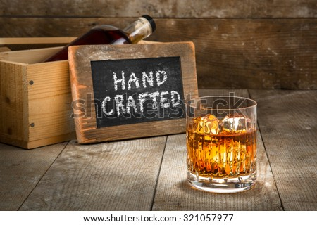 Hand crafted small batch craft liquor glass bourbon whisky scotch brandy rum on wooden rustic surface whiskey - stock photo