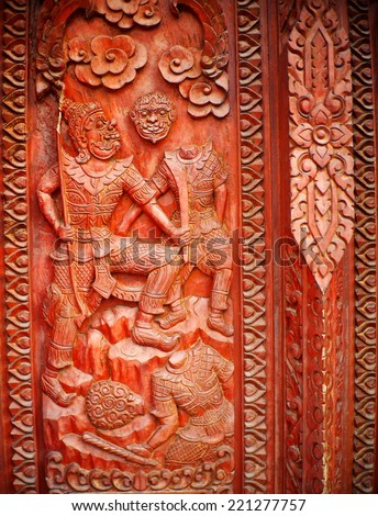 hand crafted work of THAI artist on a red brown hardwood temple door plate showing typical traditional pattern ornaments, tree, human, animals and god figures for buddhism temple decoration - stock photo