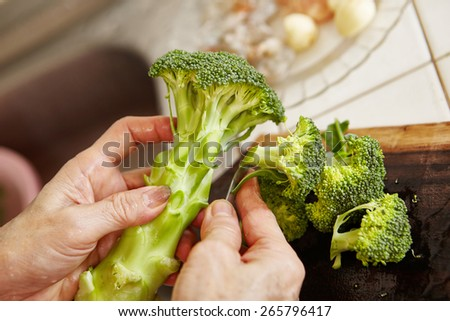 Hand cutting the broccoli used for cooking - stock photo