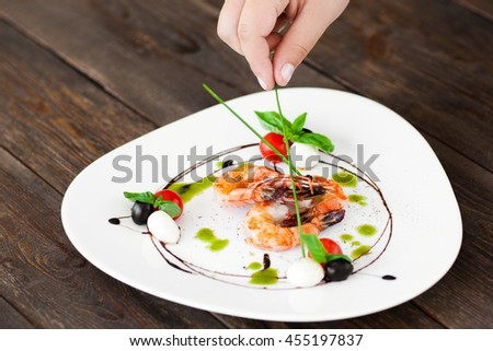 Hand decorated plate with grilled shrimps with green sticks, dark wooden background. Food preparation before serving at restaurant - stock photo