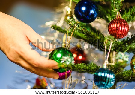 hand decorating a christmas tree - stock photo