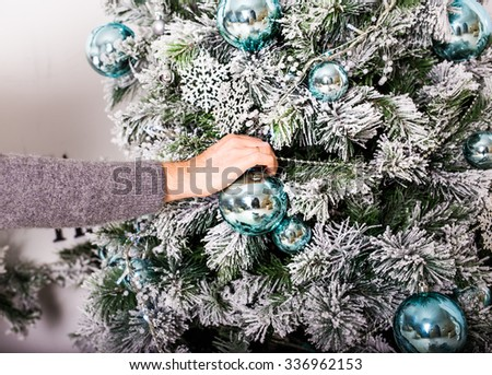 hand decorating a christmas tree - stock photo
