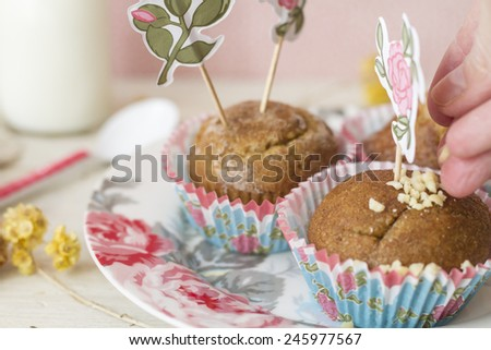 Hand decorating with mandel delicious breakfast compound of whole  muffins on flowered dish accompanied by milk - stock photo