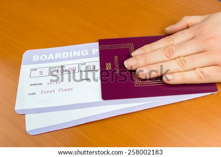 hand delivering passport and boarding pass - stock photo