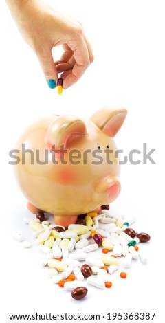 Hand deposing pill into piggy bank isolated on white - stock photo