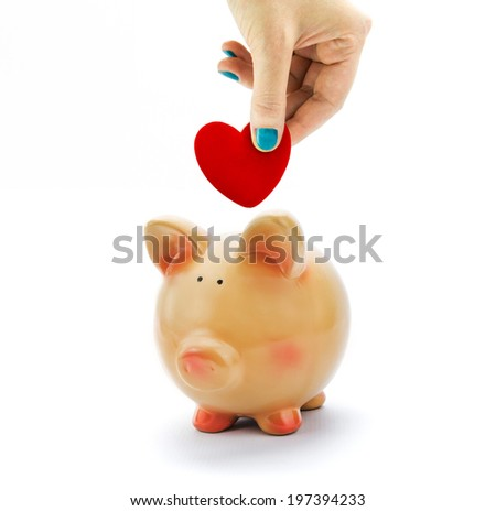 Hand deposit red heart in piggy bank isolated - stock photo
