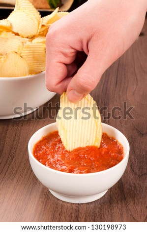 Hand dipper potato chips in the salsa sauce - stock photo