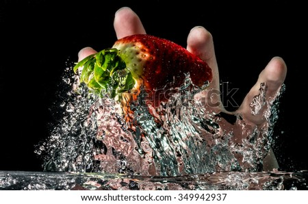 Hand dipping strawberry under water. Wash fruit. - stock photo
