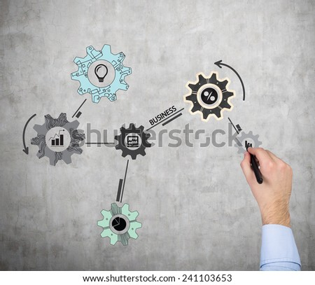 hand drawing cogwheel and gears on wall - stock photo