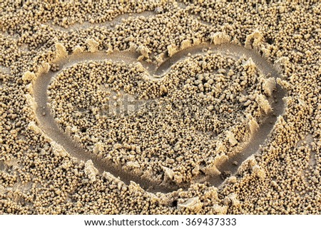hand drawing heart on small round pellets of sand beach. - stock photo