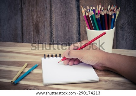 Hand drawing in open notebook on table - stock photo