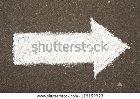 Hand drawn arrow on asphalt - stock photo