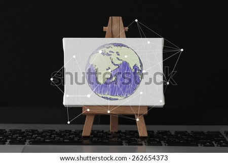 hand drawn globe with social network diagram on canvas and wooden easel on laptop computer as concept - stock photo