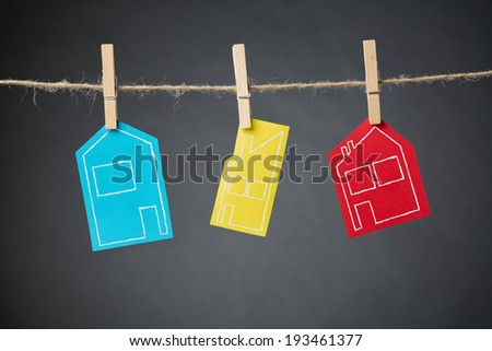 Hand drawn outlines of different types of houses on colorful pieces of paper hanging with clothespins from a rope line. - stock photo