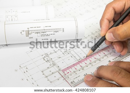 Hand engineer holding a pencil, writing on the blueprint of construction industry . Place the rolls on a desk over blurred blueprint for construction industry background. construction industry concept - stock photo