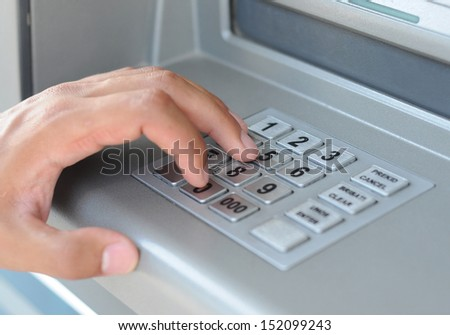 Hand entering PIN code at ATM machine - stock photo