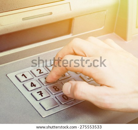 Hand entering PIN numbers on ATM bank machine - stock photo