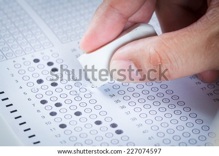 hand erase wrong answer on  Exam carbon paper computer sheet - stock photo