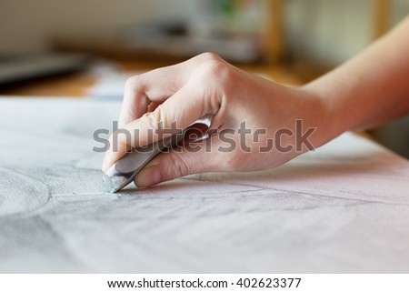 Hand erasing pencil - stock photo