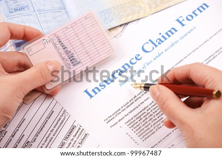 Hand filling in insurance claim form. Other papers like ID or vehicle documents in the background - stock photo