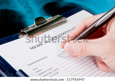 Hand filling in medical questionnaire form in a clipboard on Xray photo of lungs  - stock photo