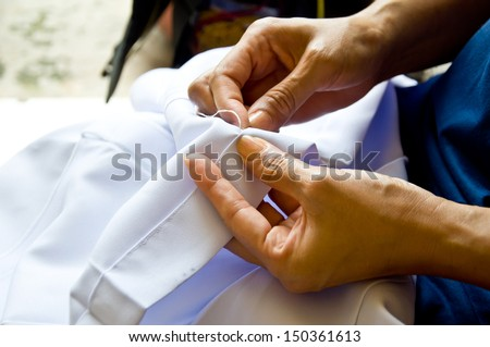 hand for sewing from woman hand - stock photo