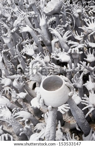 Hand from hell - Buddhist architecture in front of Buddhist white temple, Wat Rong Khun, Thailand - stock photo
