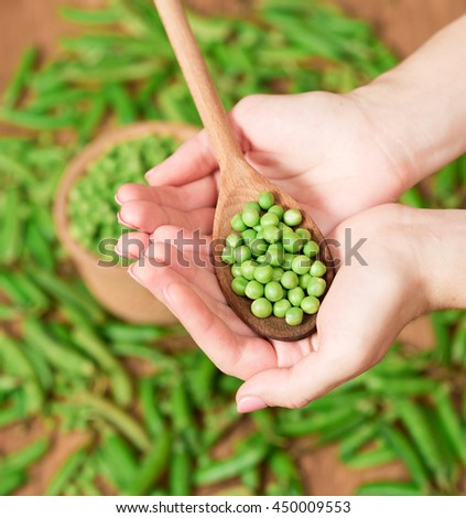 Hand full with spoon peas. Green pea pods and peas - stock photo