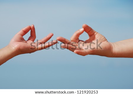 Hand gesture - Mudra - on the sky background, mother and child hand - stock photo