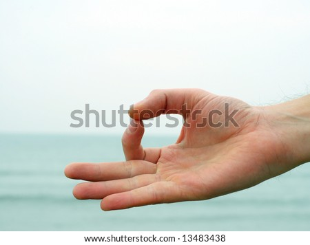 Hand gesture - Mudra - with sea on the background - stock photo