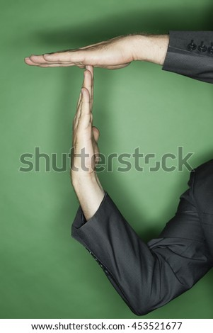 hand gesture of a male caucasian in a business suit: two hands showing T for time out - stock photo