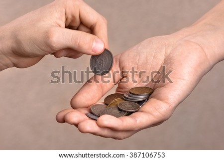 hand giving a coin to another person  - stock photo