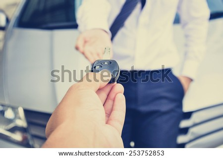 Hand giving car key to a man with car background - vintage (retro) style color effect - stock photo