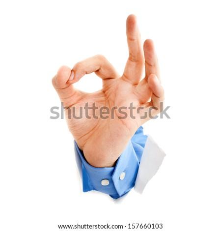 Hand giving ok sign from a ripped hole in a white paper background  - stock photo