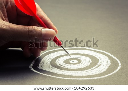 Hand going to take dart into the center of sketching dartboard - stock photo