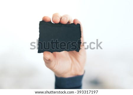 Hand gripping blank crafted business card with uneven edges on white background. Mock up - stock photo