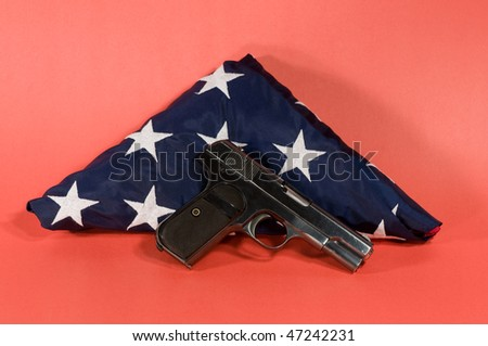 hand gun laying on  a folded american flag with a red background - stock photo