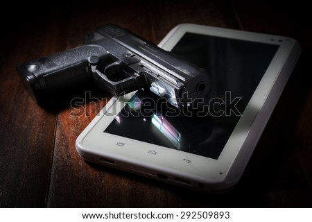 Hand gun on computer tablet. - stock photo